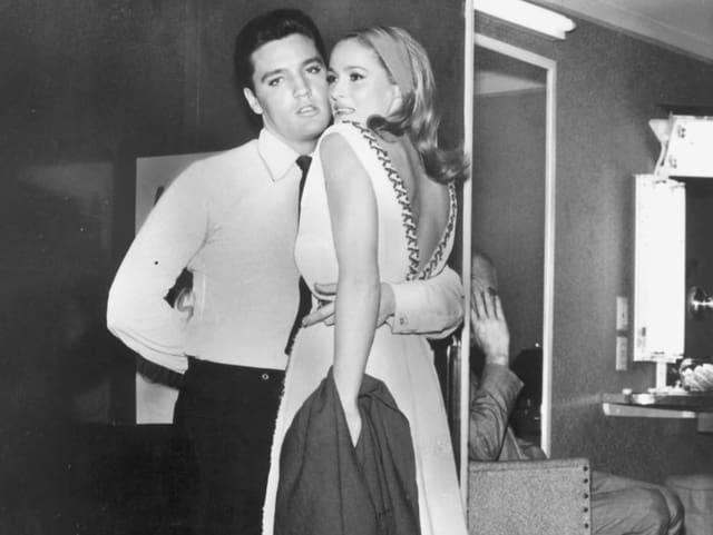 Eine Frau und ein Mann stehetn Arm in Arm vor der Kamera.