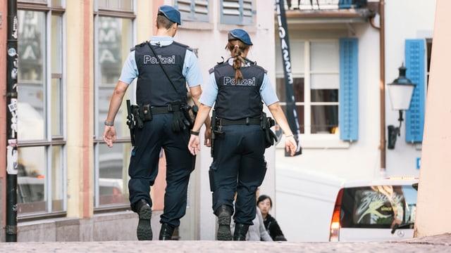 Mann und Frau in Polizeiuniform laufen durch Strasse.