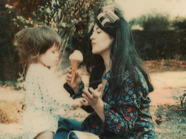Mutter und Tochter sitzen auf einer Wiese. Die dunkelhaarige junge Frau trägt Lockenwickler im Haar und hölt ein Eis in der Hand. Das Kind fasst nach der Mutter.