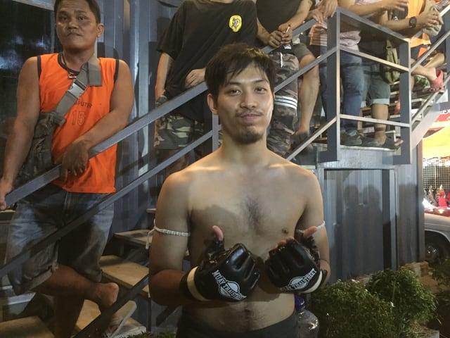 Ein junger Mann mit nacktem Oberkörper dünnen Kampfhandschuhen und Mundschutz.