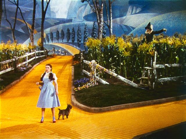 Judy Garland, Toto, Ray Bolger in einer Szene auf einem leuchtend gelben Weg.