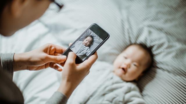 Ein Mann macht ein Foto von seinem Kind.