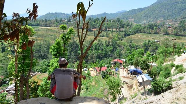 Ein Mann sitzt im Schatten und blickt auf das Dorf.