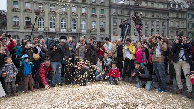 Eine Menschenmasse sammelt sich um die ausgeleerten Fünfräppler auf dem Bundesplatz