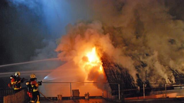 Feuerwehrleute löschen einen Brand eines Einfamilienhauses