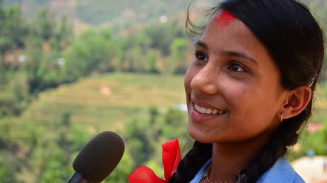 Ein Mädchen mit rotem Punkt auf der Stirn spricht in ein Mikrofon.