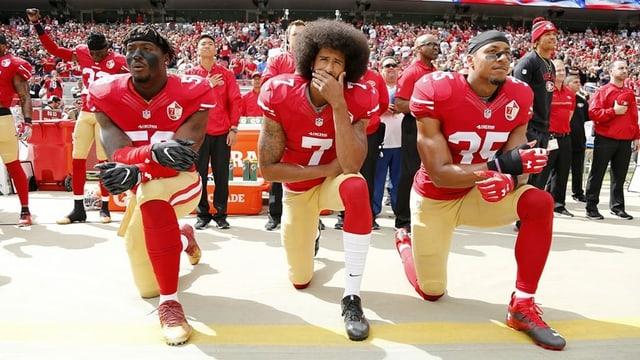 Football-Spieler Colin Kaepernick und zwei Teamkollegen knien während der Hymne.