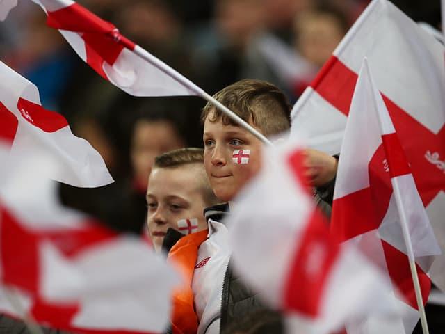 Knaben schwingen die englische Flagge.