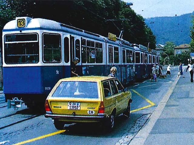 Ein Auto steht hinter einem Tram.
