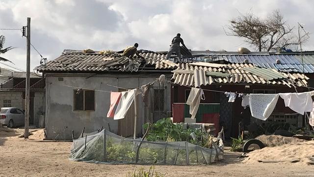 Zerstörtes Haus, Männer die das Dach reparieren