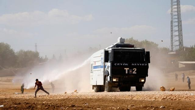 Ein Polizeifahrzeug setzt einen Wasserwerfer gegen kurdische Demonstranten ein.
