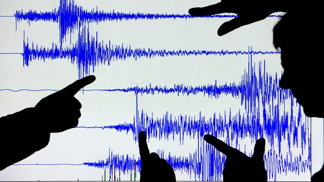 Silouetten von Händen zeigen auf eine Grafik mit seismographischen Ausschlägen.