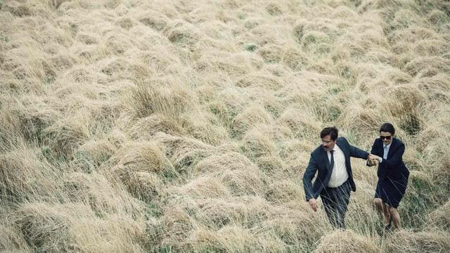 Mann und Frau laufen durch trockendes Gras.