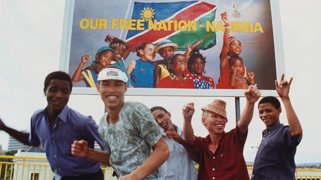 Junge Männer tanzen unter einem Schild, auf dem steht: Our free Nation - Namibia.