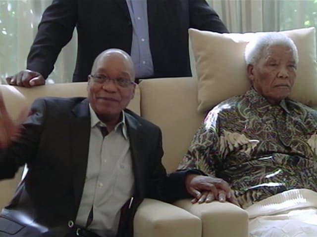 Zuma hält Mandelas Hand und winkt in die Kamera. Mandela wirkt apatisch, ein Kissen stützt seinen Kopf