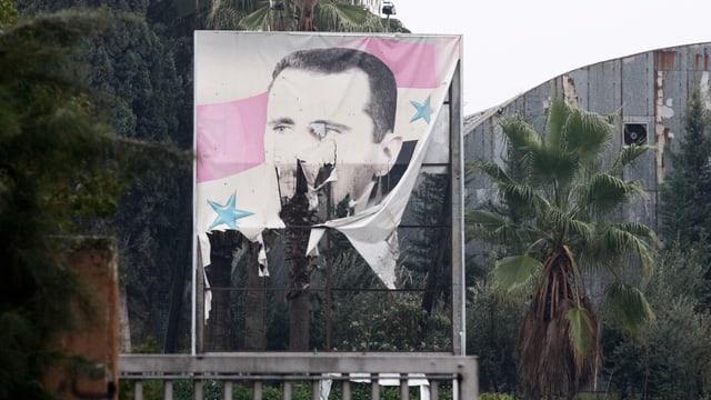 Ein halbzerrissenes Plakat von Assad steht für den Zustand seines Regmies.