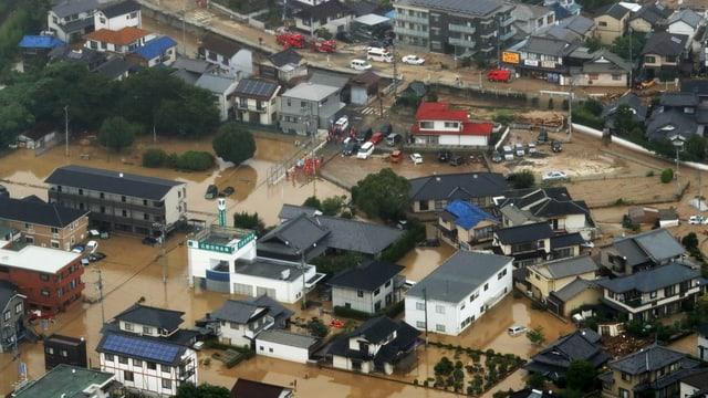 Las vias en la metropola giapunaisa da Hiroshima èn inundadas.