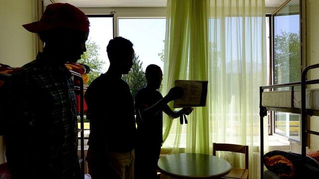 Junge Männer in einem Zimmer aufgenommen. Fotografie mit Gegenlicht. Personen sind nicht erkennbar
