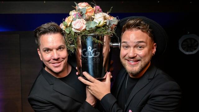 Zwei Männer in schwarzen Jacketts mit Blumenstrauss in der Mitte
