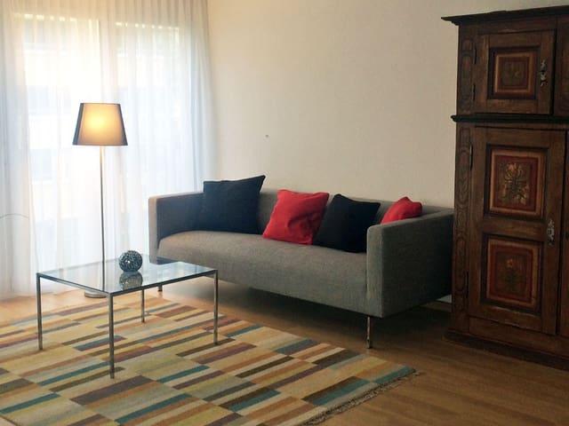 Eine graue Stoffcouch steht neben einem dunklen Holzschrank, davor ein Glastisch, eine Ständerlampe und ein farbiger Teppich.