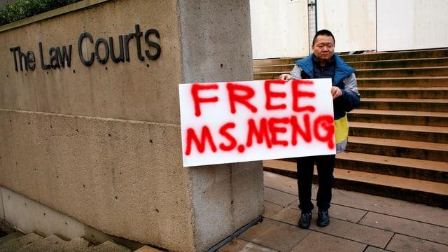 Mann, der ein Plakat hält. Darauf steht: «Free Ms. Meng»