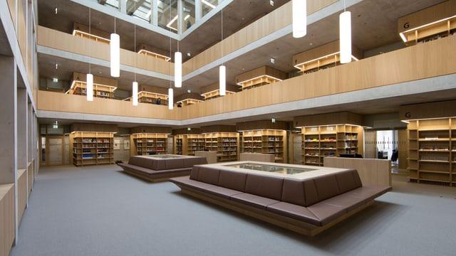 Blick ins Innere der Bibliothek, in der Mitte Leseplätze, am Rand Bücherregale.