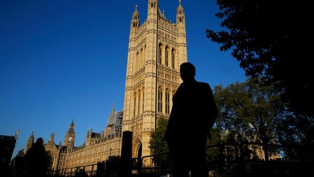 Ein Mann steht vor dem Parlamentsgebäude in London.