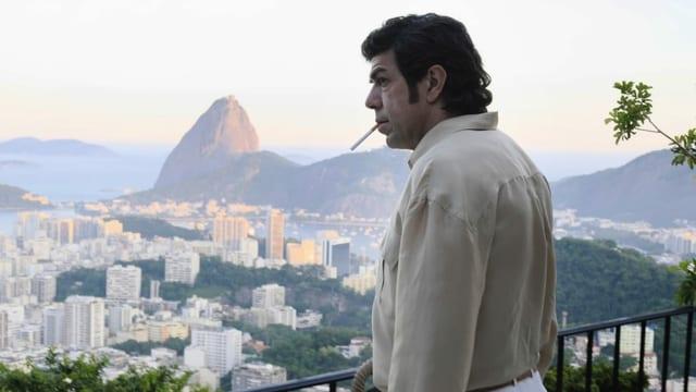 Ein Mann raucht eine Zigarette, im Hintergrund erkennt man Rio.