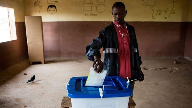 Malischer Bürger steckt einen Wahlzettel in eine Wahlurne.