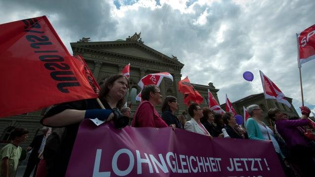 Frauen mit Transparenten und Flaggen, im Hintergrund das Bundeshaus.