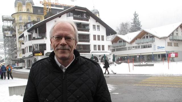 Ein Mann mit schwarzem Mantel, grauen Haaren und Brille auf einem verschneiten Trottvoir.