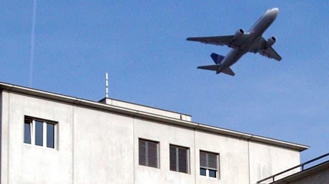 Ein Flugzeug fliegt über ein Gebäude
