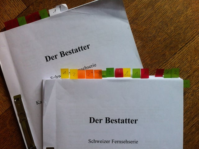 Zwei Drehbücher mit dem Titel «Der Bestatter». In den Büchern sind einige Seiten mit farbigen Post-Its markiert.