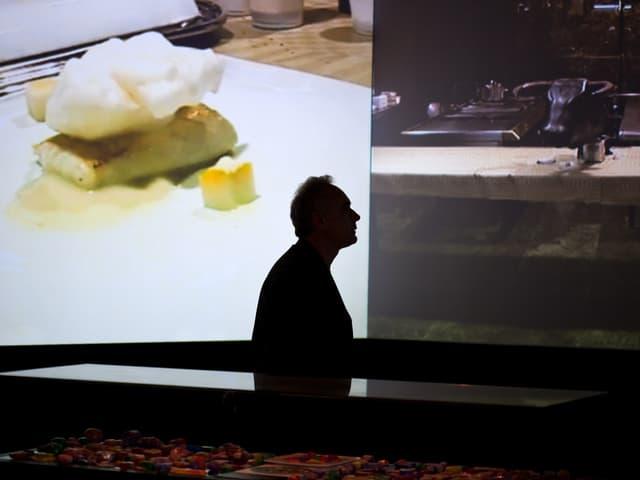 """Der Koch ist als Schatten zu sehen vor zwei Bildern: Eines zeigt einen Teller mit einer seiner Kreationen, das andere sein Restaurant """"El Bulli""""."""