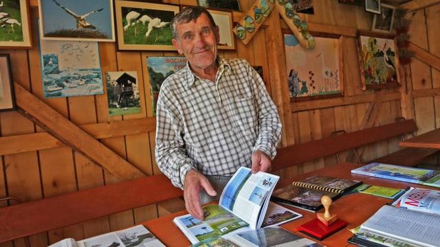 Włodyslaw Andrejew blättert in einem Buch. Hinter ihm sind Bildern mit Störchen.