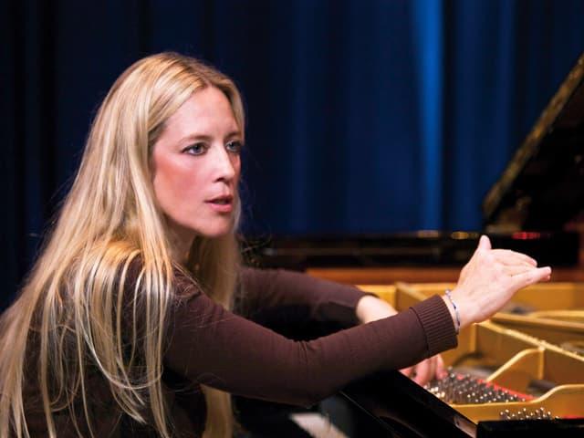 Eine blonde Frau am Klavier.