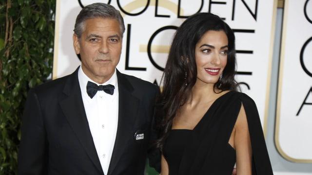 George Cloney posiert im schwarzen Anzug mit Fliege zusammen mit siner Frau Amal.