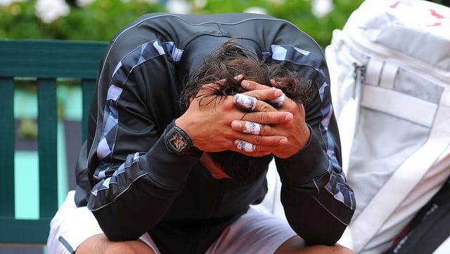Rafael Nadal kauert auf einer Bank.