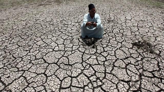 Ein Bauer hockt auf ausgetrockneter Erde.