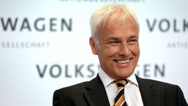 Matthias Müller lachend vor Volkswagen-Schriftzug