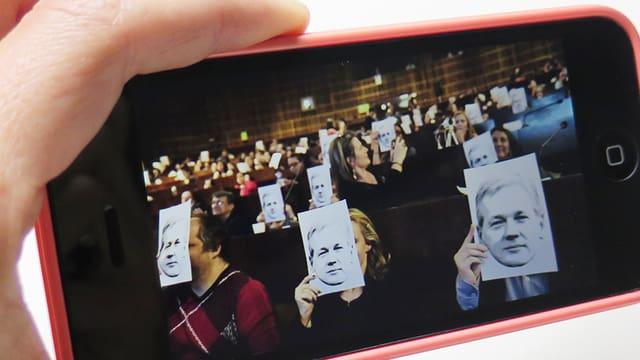 Ein Handy zeigt ein Foto, auf dem Teilnehmer einer Konferenz sich das Bild von Julian Assange vors Gesicht halten.