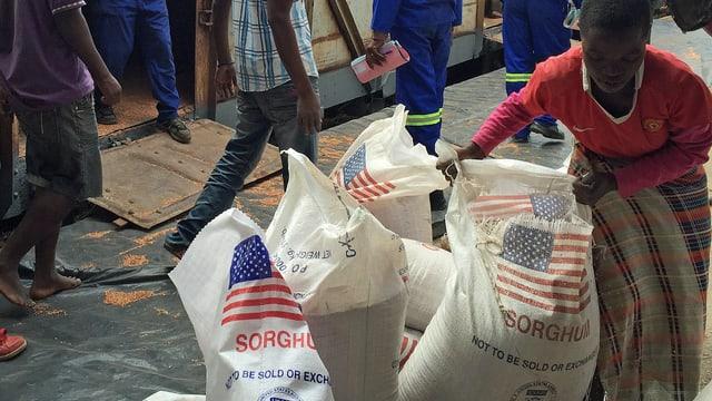 Man stapelt Hirsesäcke des Welternährungsprogramms mit der aufgedruckten US-Flagge