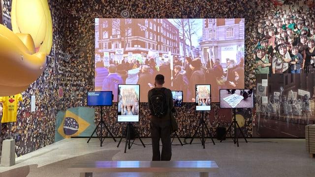 Raum in einem Museum. An der Wand ein grosses Bild einer Menschenmenge, auf verschiedenen Bildschirmen sind Demonstrationen zu sehen. Ein einzelner Mann steht im Raum und schaut auf die Bildschirme.