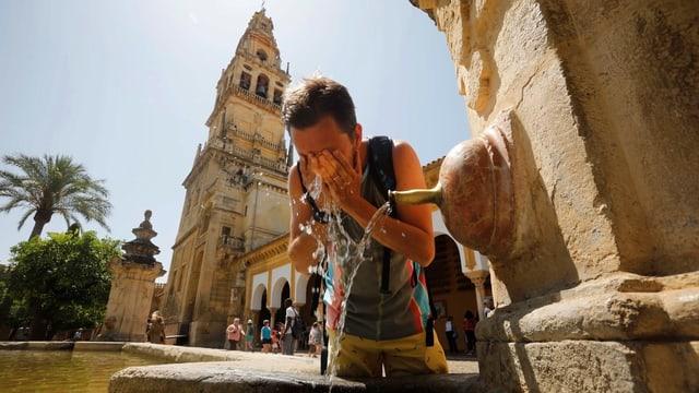 Mann benetzt sich das Gesicht an einem Wasserstrahl. Im Hintergrund ein Turm.