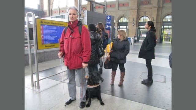 Mann mit Blindenstock und Blindenhund im Zürcher Hauptbahnhof.