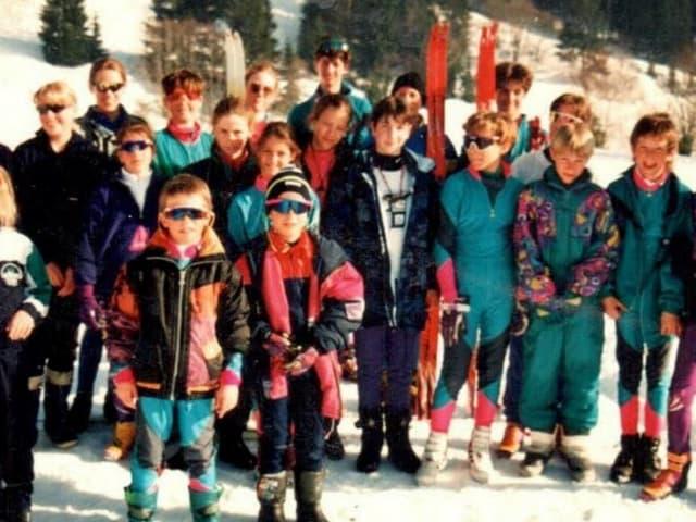 Eine Gruppe von Kindern in Skikleidern steht im Schnee.