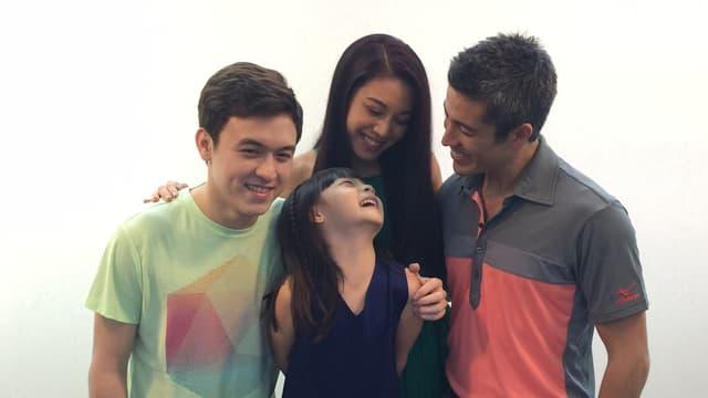 Ein Mann, eine Frau, ein Junge und ein Mädchen mit asiatischem Aussehen lächeln sich gegenseitig an.