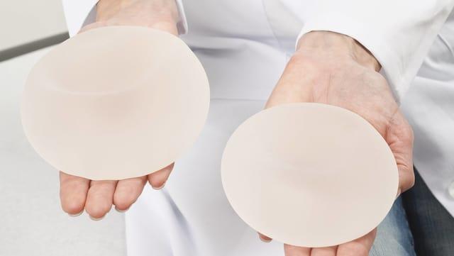 Symbolbild: Brustimplantate auf zwei Händen.