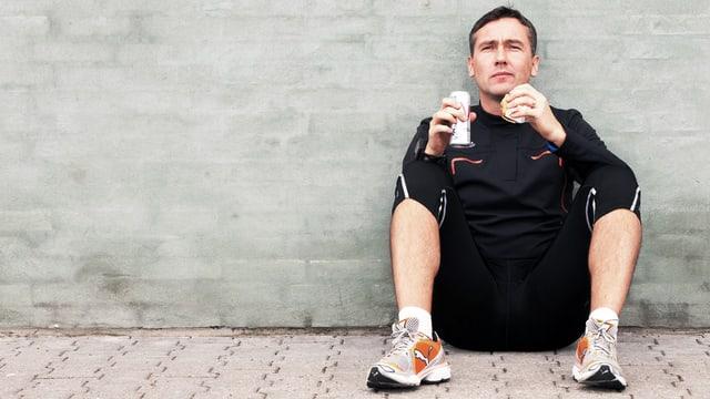 Ein Mann in Joggingausrüstung sitzt an eine Hauswand gelehnt auf dem Boden und isst ein Brötchen und trinkt aus einer Dose.
