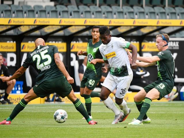 Breel Embolo setzt sich gegen mehrere Wolfsburger durch.